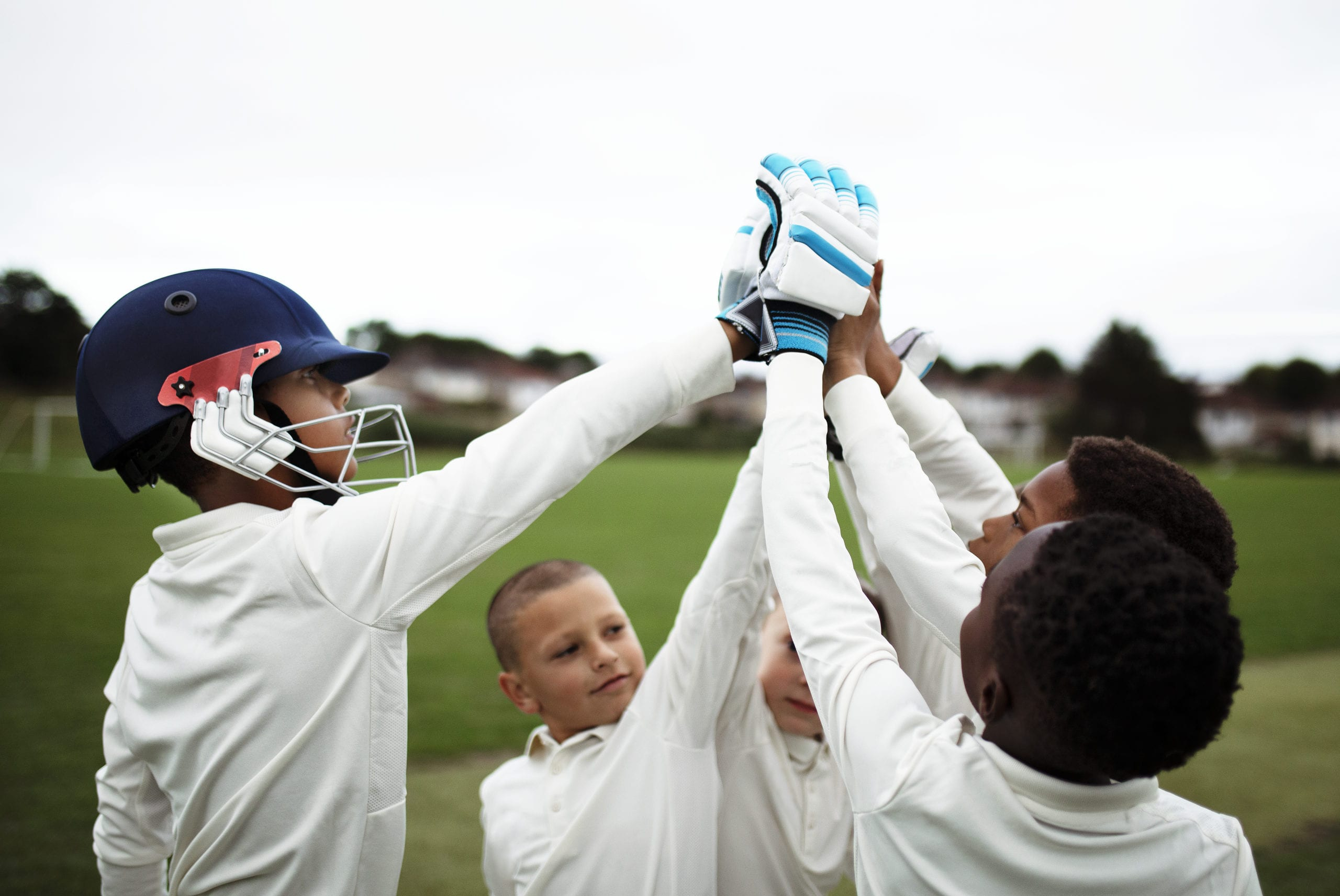 5 kids in cricket gear high fiving