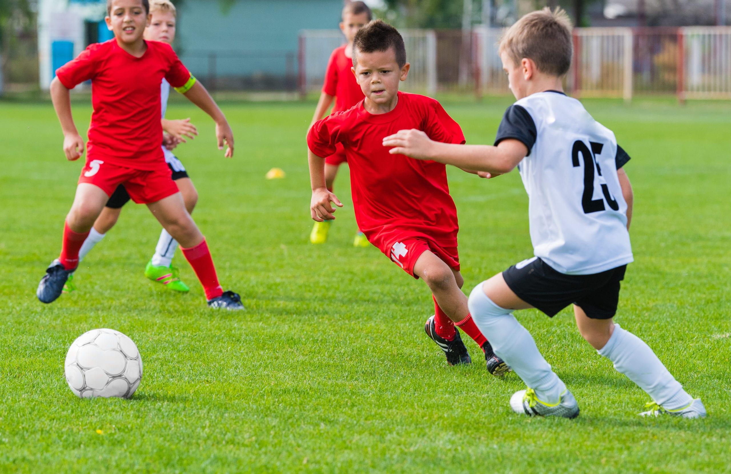 boys kicking soccer ball on the sports field austin